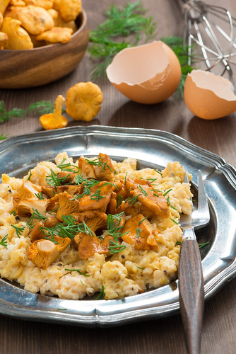 delicious scrambled eggs with chanterelles and fresh dill, vertical