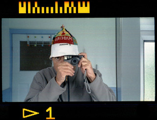 reflected self-portrait with Nikon Nuvis 75 camera and Madeira-Skoda hat