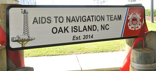 A new sign is unveiled Tuesday Sept. 30, 2014 during a commissioning ceremony for the new Aids to Navigation Team Oak Island at Coast Guard Staton Oak Island..  Rear Adm. Stephen P. Metruck, 5th District commander, officially designated Petty Officer 1st Class Ryan R. Yoraschek as officer in charge of the ANT Oak Island unit during the ceremony.  (U.S. Coast Guard photo by Petty Officer 3rd Class Nate Littlejohn)