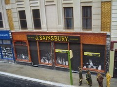 "A model of a terraced shop with four people waiting at a bus stop just outside.  The frontage reads ""J. Sainsbury. Head Depot Blackfriars.""  Advertising stickers in the windows read ""Sainsbury's win on points""."