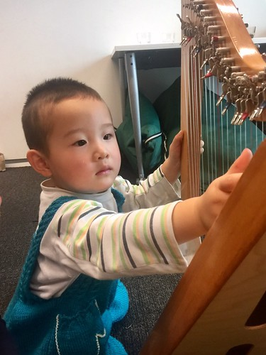 Child tries out the harp, Upper Riccarton Library