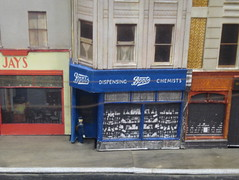 "A model of a shop slightly protruding from a terrace, with a blue frontage and white writing on top reading ""Boots Dispensing Chemists""."