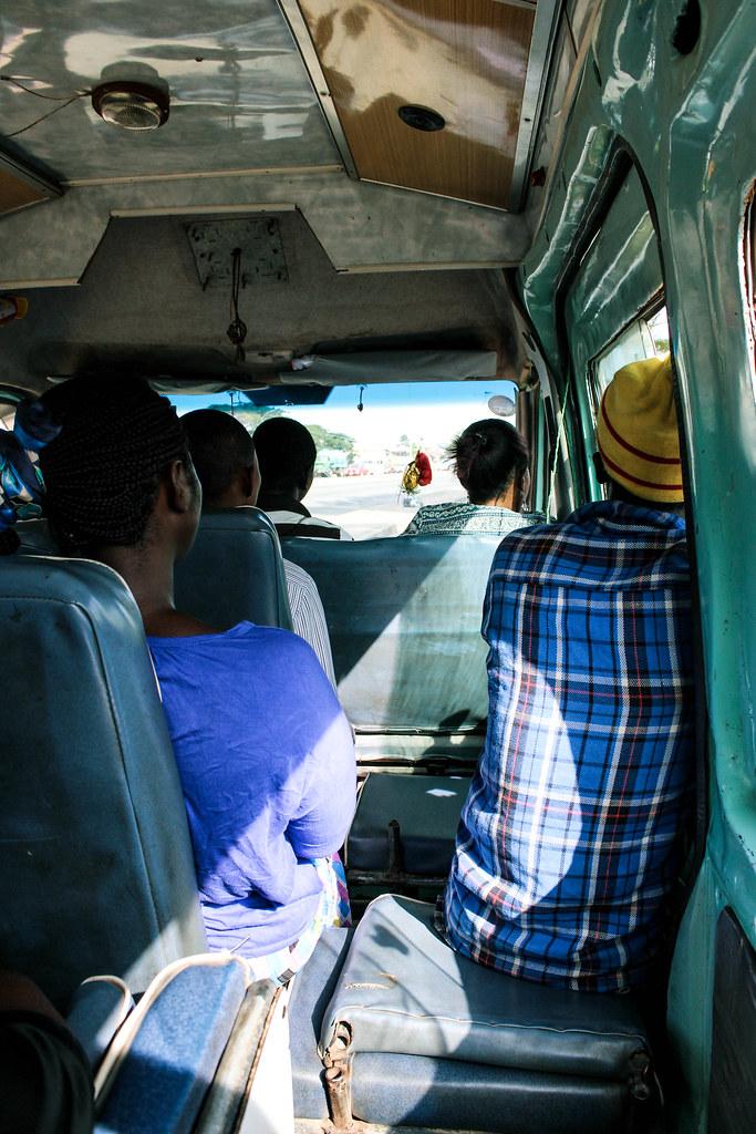 Der Conductor, hier in einem Tro-Tro auf einer Einfallstraße nach Accra, bedient die Schiebetür und kassiert den Fahrtpreis.