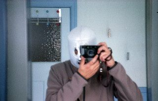 reflected self-portrait with Ricoh FT-200 camera and mask