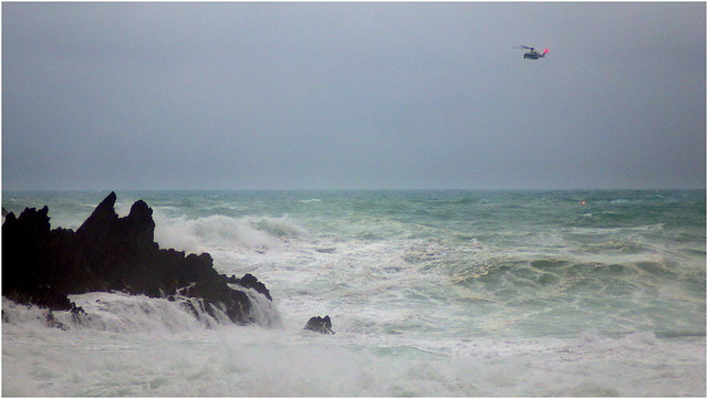 JAPAN COAST GUARD HELICOPTER DROPS A FLARE BESIDE THE LIFELESS, FLOATING BODY OF A U.S. AIRMAN WHO WAS WASHED INTO THE SEA