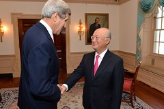 U.S. Secretary of State John Kerry greets Director General of the International Atomic Energy Agency Yukiya Amano before their bilateral meeting at the U.S. Department of State in Washington, D.C., on October 30, 2014. [State Department photo/ Public Domain]