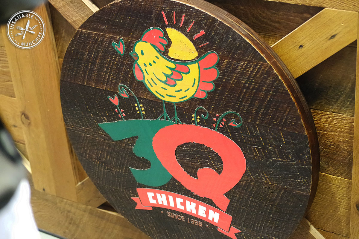 Wooden sign for 3Q chicken mounted onto the side of the front counter.