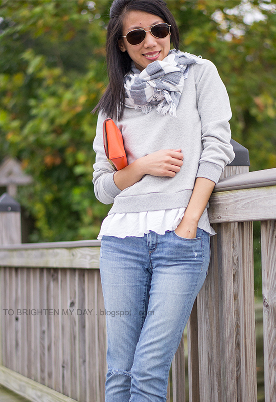rugby striped scarf, gray ruffled sweatshirt, orange clutch