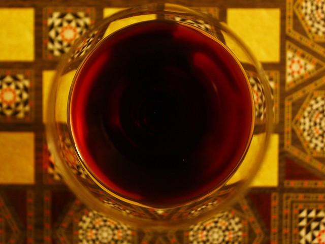 a glass of wine on a backgammon board