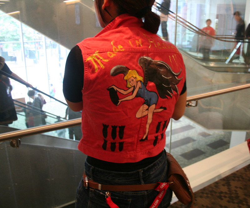 a cosplayer wears a bright red, handpainted vest