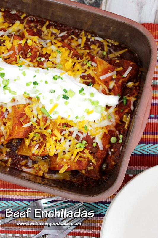 Beef Enchiladas in a baking pan with forks.