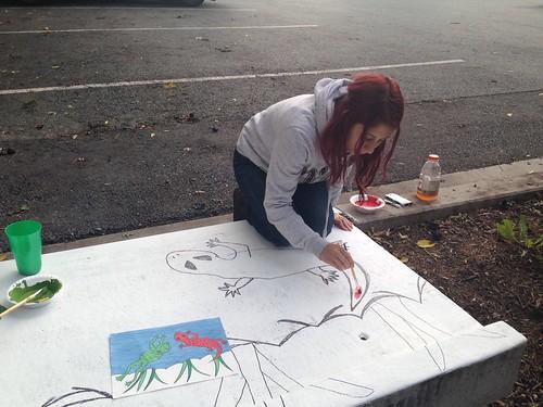 Image of a volunteer painting a salamander.