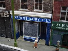 "A model of a ground-floor terraced shopfront with a sign reading ""Express Dairy Co. Ltd.""."