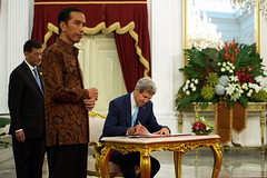 President Joko Widodo of Indonesia waits as U.S. Secretary of State John Kerry signs a guest book after he came to the Presidential Palace in Jakarta for a bilateral meeting following inauguration ceremonies for the newly sworn in leader on October 20, 2014. [State Department photo/ Public Domain]