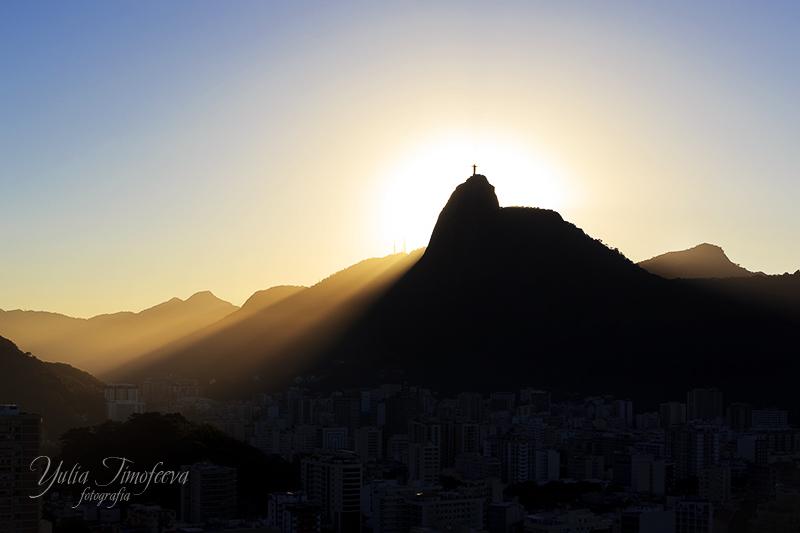 Sun light behind Mountain Corcovado Christ the Redeemer, sunset, Rio de Janeiro