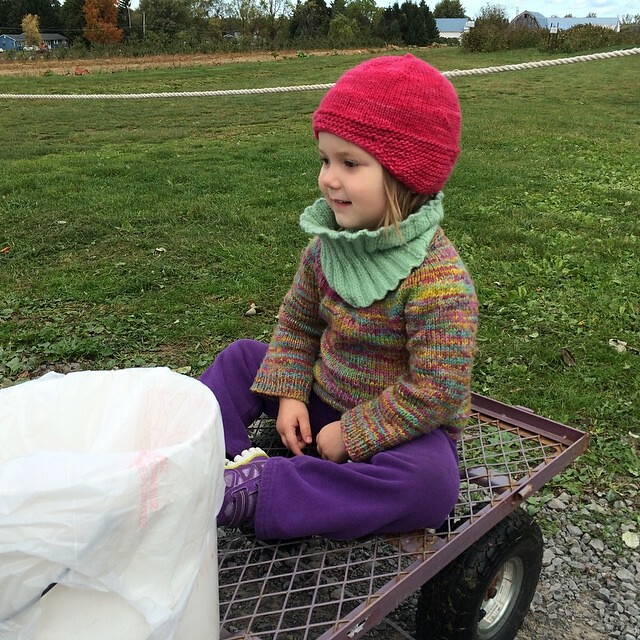 On the wagon with her apple bucket.