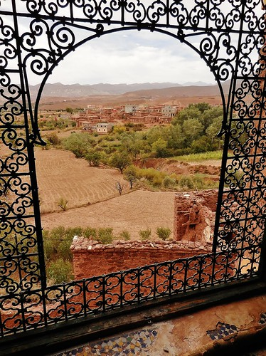 africa morocco atlasmountains kasbahtelouet castle fortifieddwelling fortress window grille metalwork view countryside landscape buildings houses village trees soil farm mosaics tiles