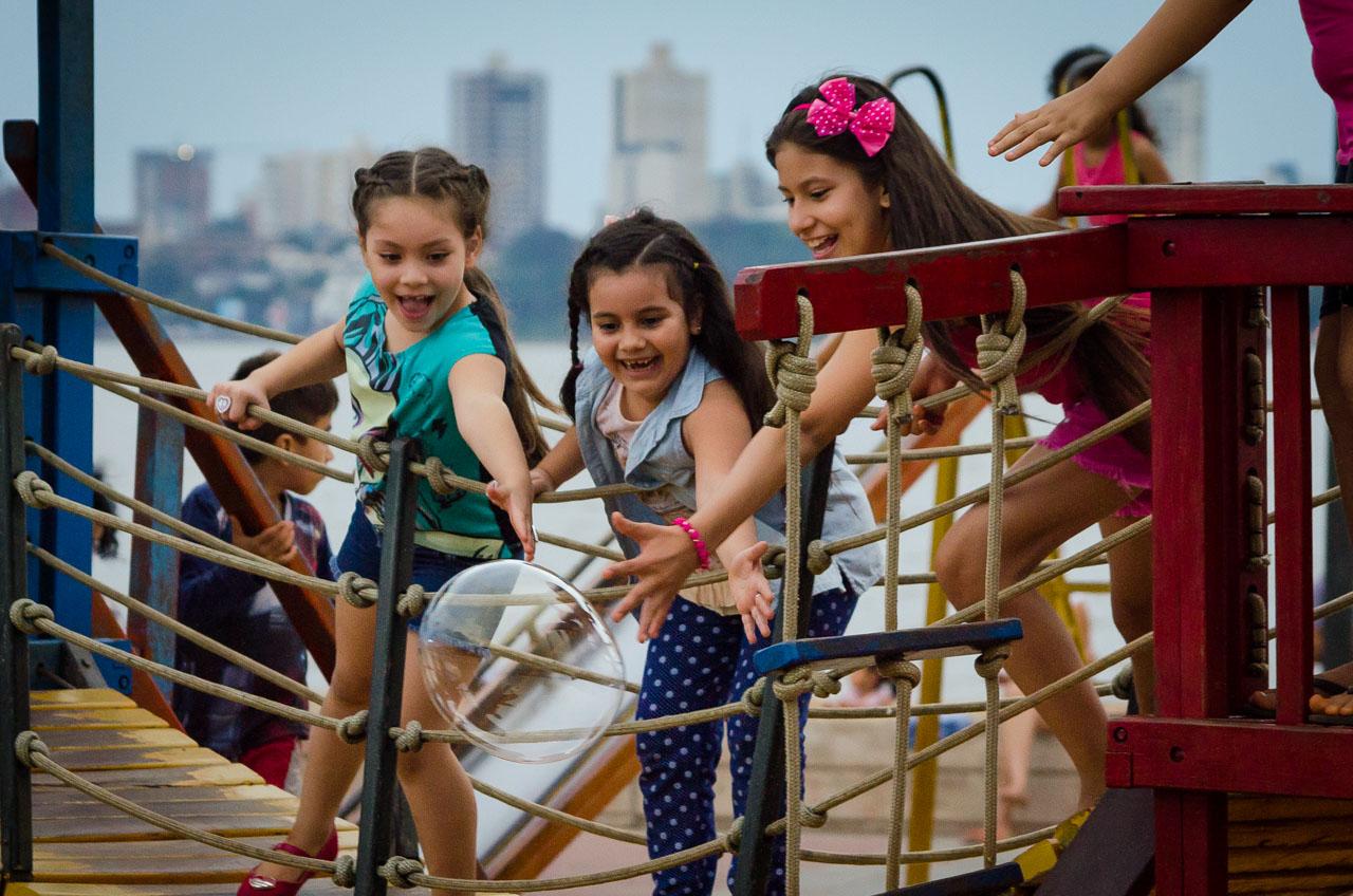 Niñas se divierten mientras pretenden agarrar burbujas de jabón en un parque de la costanera de Encarnación, en el domingo de pascuas. (Elton Núñez).