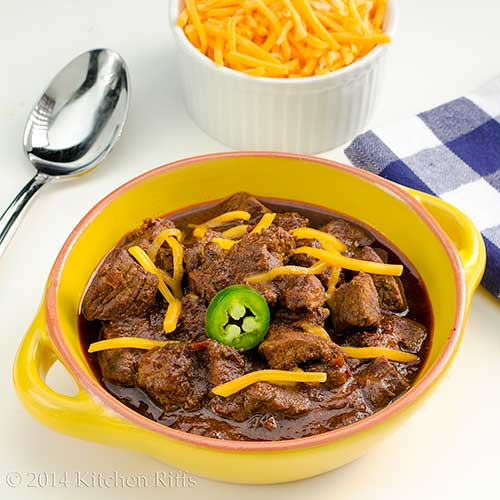 Texas-Style Chili con Carne with jalapeno and cheddar cheese garnish