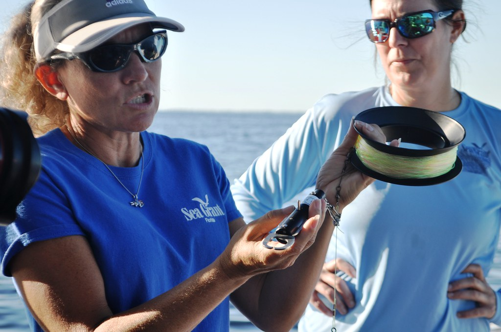Florida Sea Grant Extension Agent Betty Staugler Displays s a Descending Device While Extension Agent Joy Hazell Looks On.