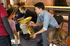 Ray Seong Jin Han shares his French Horn with a guest at Boston Children's Museum