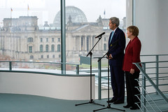Against a backdrop of the German Reichstag, U.S. Secretary of State John Kerry and German Chancellor Angela Merkel listen to a translation as the two address the U.S. and German media before a bilateral meeting at the Chancellery in Berlin, Germany, on October 22, 2014. [State Department photo/ Public Domain]