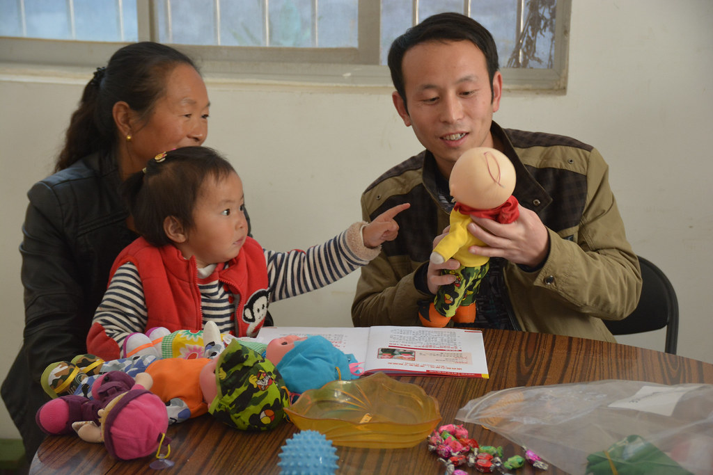 Picture of parenting instructor teaching baby and grandma in rural China