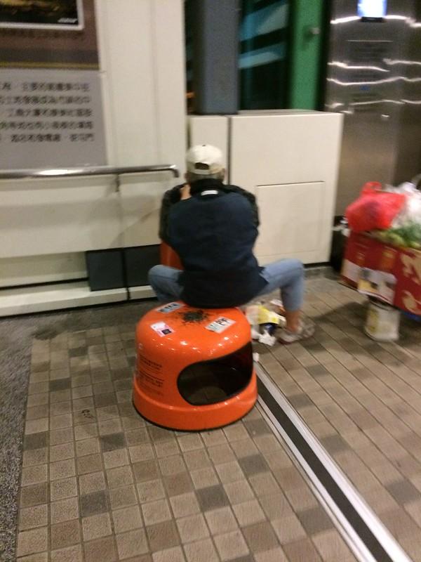 """""""執垃圾新境界。把垃圾桶上蓋放在地下當椅子坐,慢慢搜查垃圾桶內有用的東西。他們都是環保先鋒。"""""""