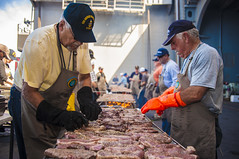Cooks from the Valley volunteers prepare steaks for Sailors aboard USS George Washington (CVN 73). (U.S. Navy/MCSN Loni Mae Lopez)