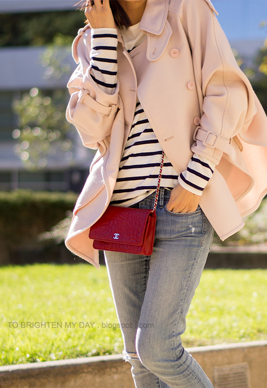 pink trench cape, striped top, distressed jeans, red crossbody bag