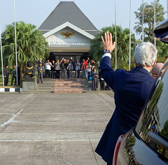 U.S. Secretary of State John Kerry waves to members of the Indonesian media as he and the rest of a delegation representing President Obama arrive in Jakarta, Indonesia, on October 20, 2014, to attend the inauguration of President-elect Joko Widodo. [State Department photo/ Public Domain]