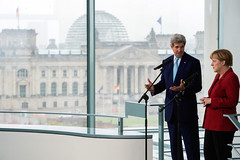 Against a backdrop of the German Reichstag, U.S. Secretary of State John Kerry speaks to German Chancellor Angela Merkel as the two address the U.S. and German media before a bilateral meeting at the Chancellery in Berlin, Germany, on October 22, 2014. [State Department photo/ Public Domain]