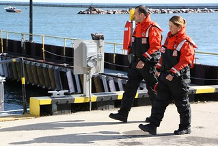Ensigns Leah C. Roach and Rian Ellis, both members of Coast Guard Sector Lake Michigan, located in Milwaukee, prepare to get underway on a response boat at the sector while wearing their cold water wetsuits, Oct. 9, 2014. Coast Guard units across the country wear protective wetsuits whenever the water temperature is below 60 F and wear drysuits when the water temperature is below 50 F. The Coast Guard recommends that boaters do the same. (U.S. Coast Guard photo by Lt. Jesse Webster)