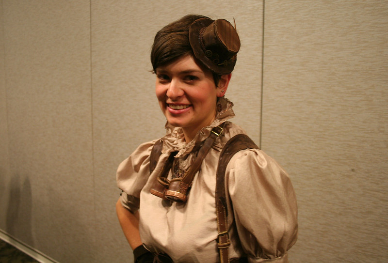 a woman wears a tiny top hat and sports steampunk suspenders