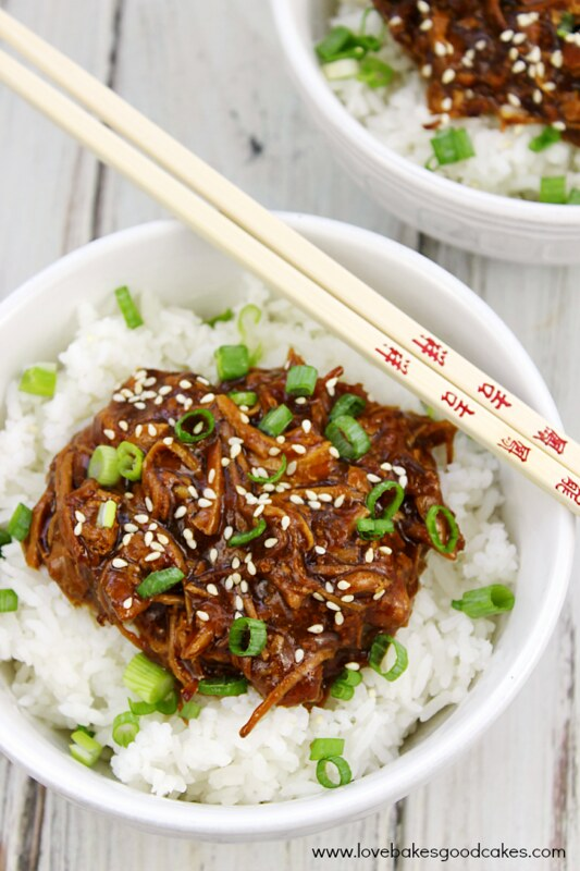 Slow Cooker Honey Sesame Chicken in a white bowl with chop sticks.