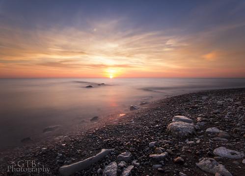 sun mist lake beach water sunrise rocks colorful long exposure michigan