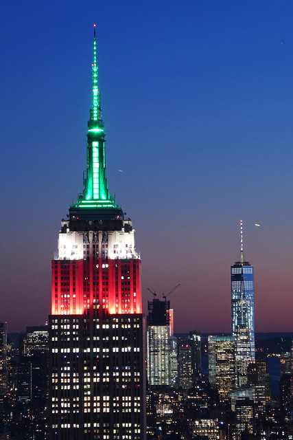 Empire State Building lighting in red, white & green in Honor of Columbus Day as seen from Rockefeller Center Observation Deck in the Theater District of Midtown Manhattan in New York City, NY