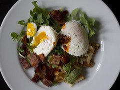 Poached eggs on top of arugula, hashed potatoes, a…