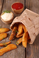 Homemade fried potato in paper bag, on wooden back…