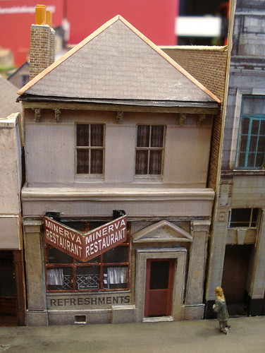 "A model of a two-storey building with a projecting sign on the ground floor reading ""Minerva Restaurant"".  Below the shop window is another sign reading ""Refreshments""."