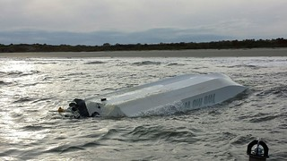 A capsized boat sinks slowly off the coast of Morris Island near Charleston Harbor, Nov. 8, 2014. Of the four people aboard, two swam safely to shore while the other two were rescued by the Coast Guard. All four were wearing life jackets. (U.S. Coast Guard photo)