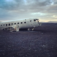 This US Navy plane crashed in Iceland in 1976. Both pilots survived and the local farmers helped themselves to the fuel and provisions (whiskey, beer). US officers stripped the plane for parts months later and it's been sitting in this Volcanic Black San