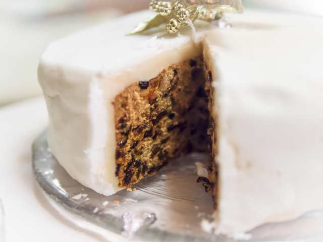 Christmas cake with slice removed and traditionally iced
