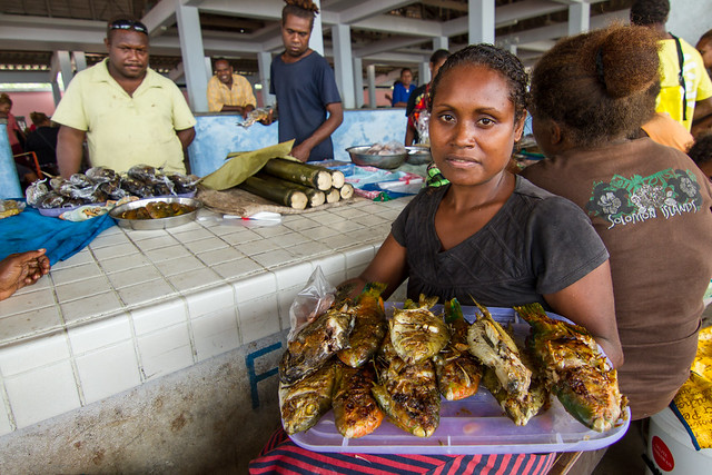A woman holds cooked reef fish for sale at her stall in Auki market, Malaita Province, Solomon Islands. Photo by Filip Milovac.