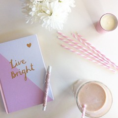 Flatlay featuring Kikki K Notebook, pen and pink striped straw