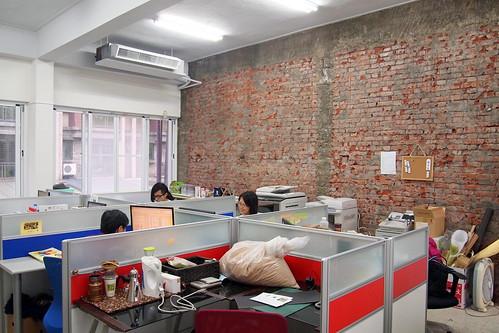 綠農的家辦公室,有大面刨除水泥的磚牆,讓人看見建築過去的肌理。攝影:李育琴。