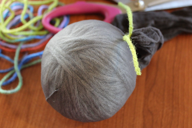 Pull the stocking around the ball tightly and tie off with craft yard to secure in place.