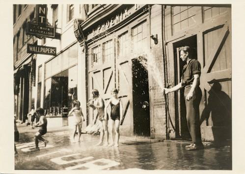 Mees trikoodes lapsi New Yorgi tänaval voolikust kastmas / Man showering children in bathing suits on a street in New York