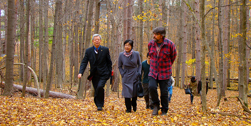 President Yang Yuliang (left) of Fudan University and Chinese Embassy Minister Counsellor Yang Xinyu (centre) tour the Queen's University Biological Station with professor Stephen Lougheed.
