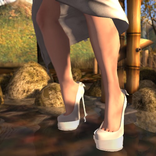 Image Description: Woman's feet, wearing white platform heels, in front of a Japanese style bamboo fountain.